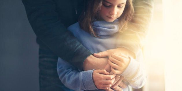 father's arms wrapped around daughter