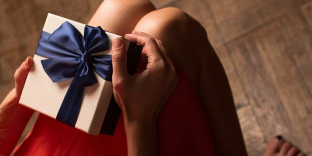 Top view woman with red dress holding a gift box with blue ribbon on her