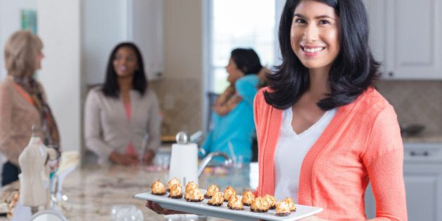 Happy woman with appetizers hosting home sales party