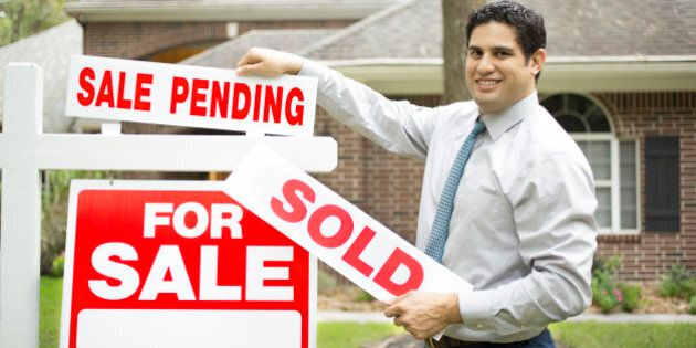 Real estate agent changes 'For Sale' sign from 'Sale Pending' to 'Sold.'. Green grass and bushes indicate...