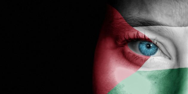A young female with the flag of Palestine painted on her face on her way to a sporting event to show...