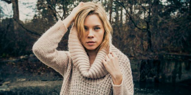 Beautiful blonde model with a large, ribbed-neck sweater by the