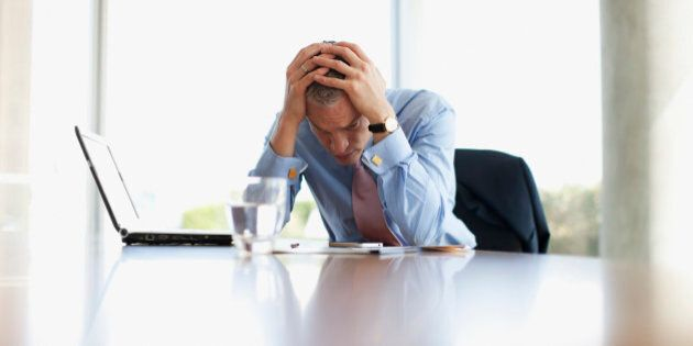Frustrated businessman with head in hands at