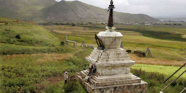 A woman stands in front of a Tibetan Buddhism ritual monument in Shangri La County, in northwestern Yunnan...