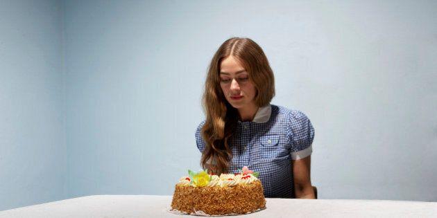 Woman sitting at table, looking at cake