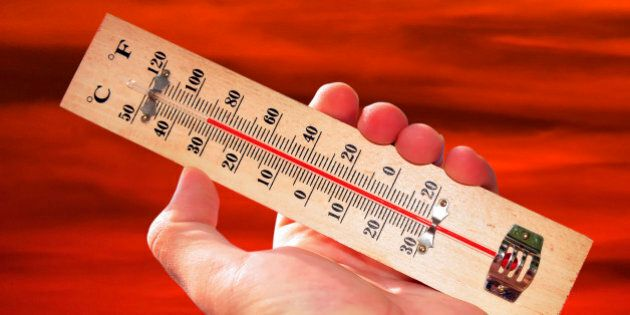 A hand and temperature scale over a red sky shows high temperatures during a heat
