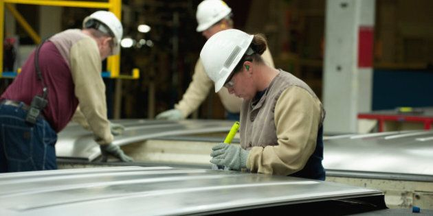 Before they are welded to assemble a mini-van body, workers inspect sheet metal components for flaws and distortions of shape.