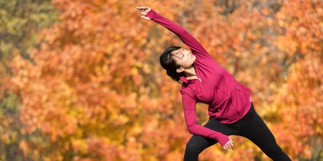 Asian runner stretching in park
