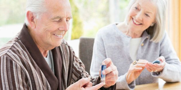 Older couple testing blood sugar