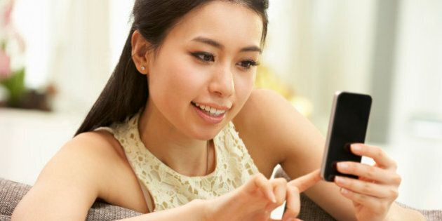 Young Chinese Woman Using Mobile Phone On Sofa At
