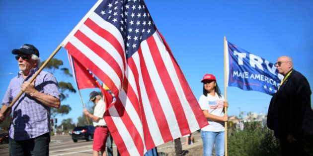 Demonstrators hold signs in support of President elect Donald Trump outside of Camp Pendleton in Oceanside,...