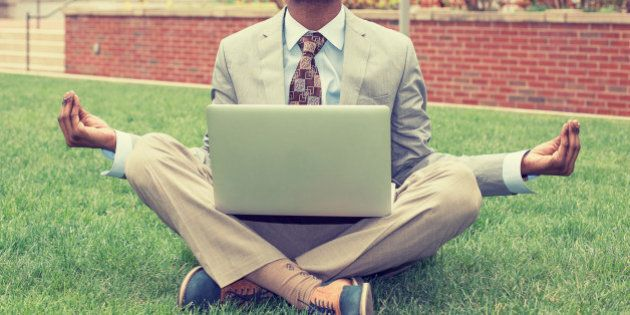 Young businessman with laptop meditating in lotus pose taking a deep breath outside corporate office....