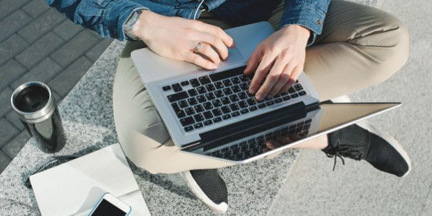 Smartphone, coffee tablet and laptop with notepad in hands of man outdoors in