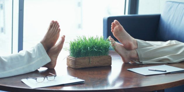 Two businesswomen resting feet on coffee table, low section, side