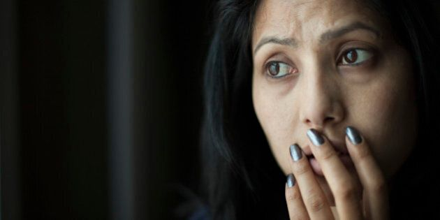 Indoor low key image of a worried and surprised Asian young woman putting her hand on her mouth and looking away at something with frowning gesture. One person, horizontal, head and shoulders composition with copy space and selective focus.