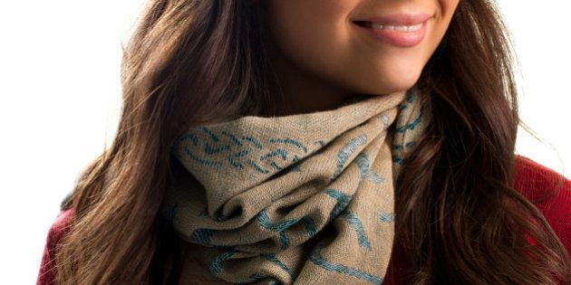 Beige scarf on woman's neck. Red garment and printed scarf. Trendy accessory for autumn outfit. Textile...
