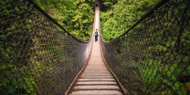 A tourist walks across the Lynn Canyon Suspension Bridge near Vancouver,