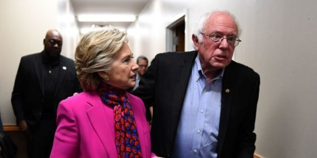 US Democratic presidential nominee Hillary Clinton talks with Bernie Sanders backstage before a campaign...
