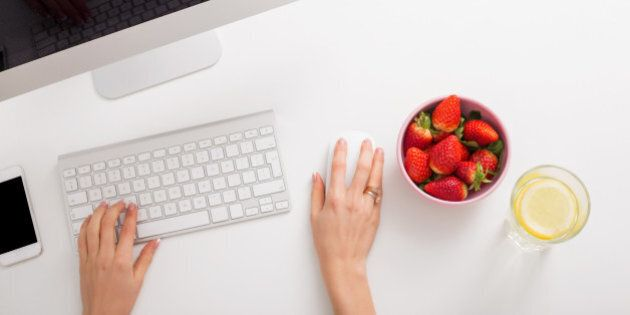 Strawberries and lemon water on office table