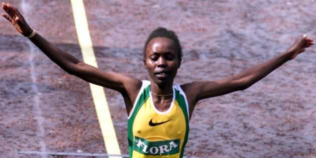 Kenya's Tegla Loroupe raises her arms in celebration as she crosses the finish line to win the women's...