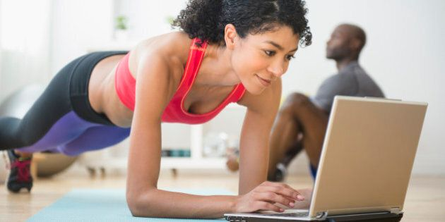 Woman using computer and doing push-ups in