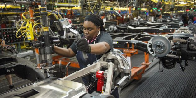 An employee secures the stabilizing bar of a sports utility vehicle (SUV) on the production line at the...