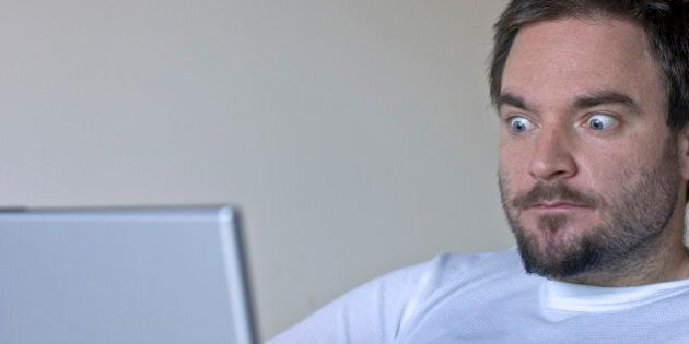 Young man in his early thirties with bulging blue eyes looking at his laptop screen in shock.