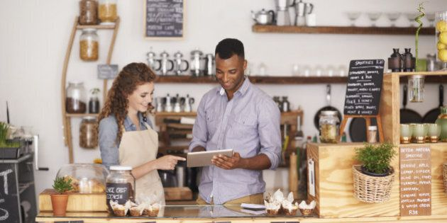 Cropped shop of a handsome coffee shop owner showing a waitress the