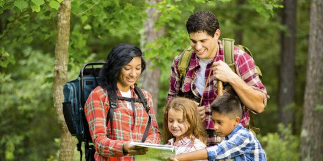 Family of four on vacation. Hiking in a national park. Southern USA. Autumn season.  Hispanic and African descent family members.  Family pauses to check the map.