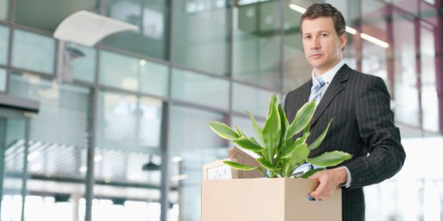 Portrait of a serious looking business executive carrying a cardboard