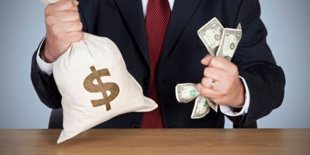 A banker sat at a desk holding a cash bag with dollar sign and gripping a fist full of dollars in the other.