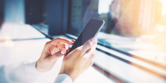 Girl touching a screen of her smarthone. Blurred