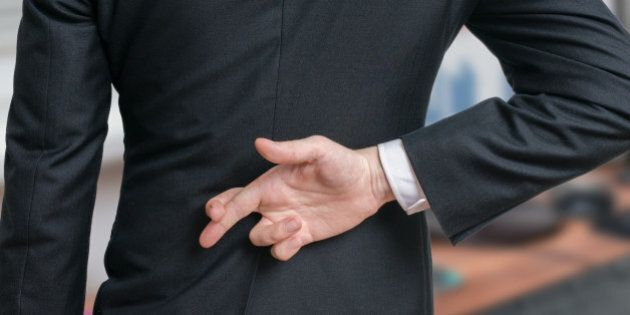 Businessman has crossed fingers behind his back. Good luck or dishonesty