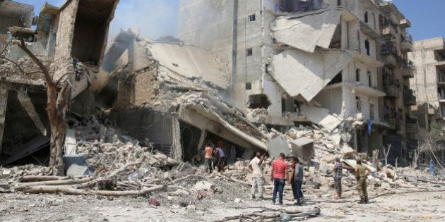 Men inspect a damaged site after double airstrikes on the rebel held Bab al-Nairab neighborhood of Aleppo,...