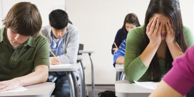 Teenage girl (16-17) sitting in examination hall, head in