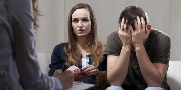 Young unhappy couple at odds on therapy