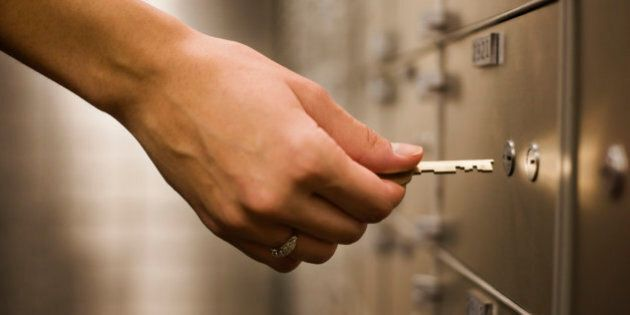 Woman's hand holding key to safety deposit box