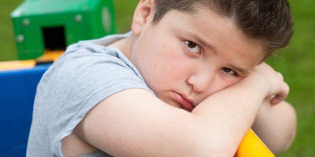 tired sad fat boy sitting on a fitness equipment