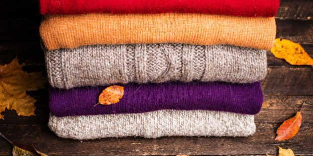 Pile of knitted winter clothes on wooden background covered with autumn leaves, knitwear, space for text....