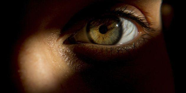 Detail of woman's eye, peering through door