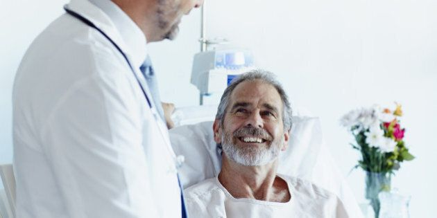 Happy mature patient looking at male doctor in hospital
