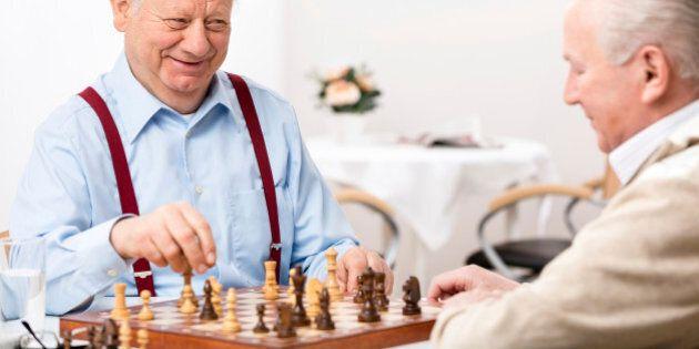 Nursing home: Senior men playing chess, focus on