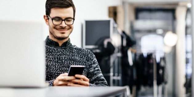 A young casual businessman wearing glasses is smiling at his smartphone in a bright modern office room....