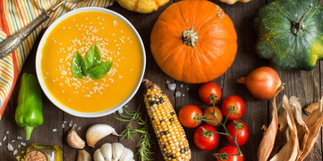 Fresh pumpkin soup and vegetables on a wooden