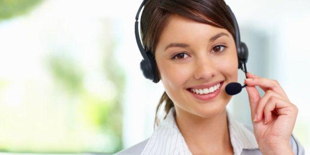 Pretty female employee speaking on headset