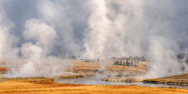 Steam rises from Grand Prismatic Spring and near river path from Firehole River, autumn. UNESCO World...