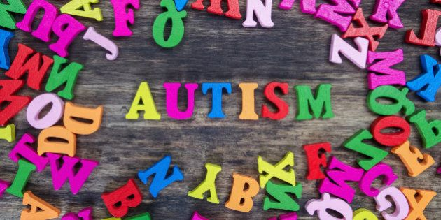 Colourful letters spelling out Autism on a wooden background