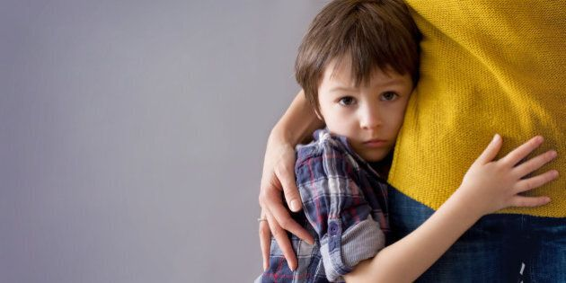 Sad little child, boy, hugging his mother at home, isolated image, copy space. Family