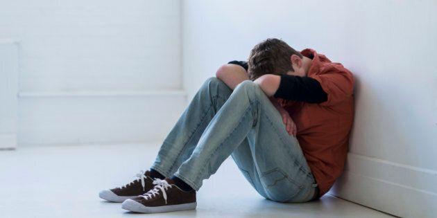 USA, New Jersey, Jersey City, Teenage boy (16-17) sitting in hallway