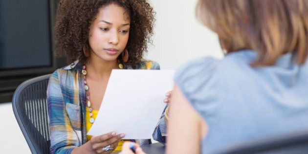 African American woman reading a resume while taking interview of a Caucasian